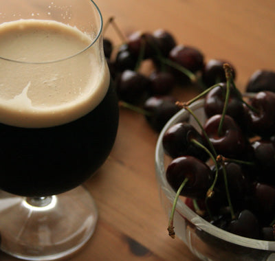 a glass of dark beer and equally dark bing cherries