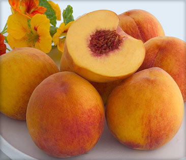 A group of peaches with one peach halved.