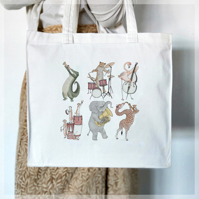 A white, 100% cotton tote bag featuring assorted african animals playing classical instruments. Illustrations by Stephanie Gray.