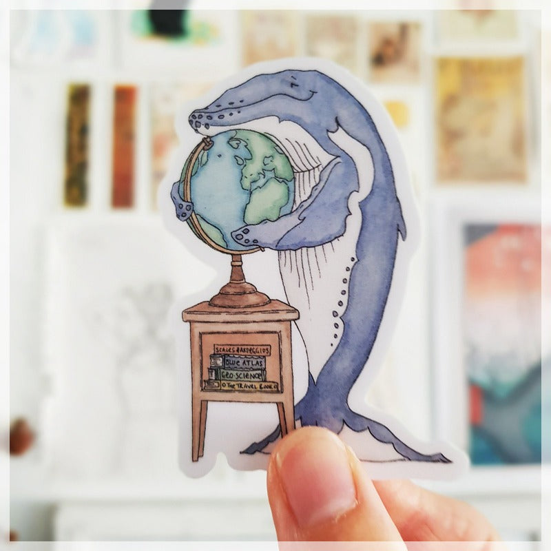 Blue the whale hugging the globe and dreaming about the next holiday she wants to go on.