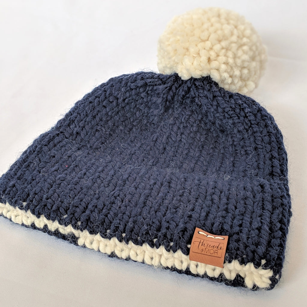 Navy and cream double brim knitted hat with yarn pompom