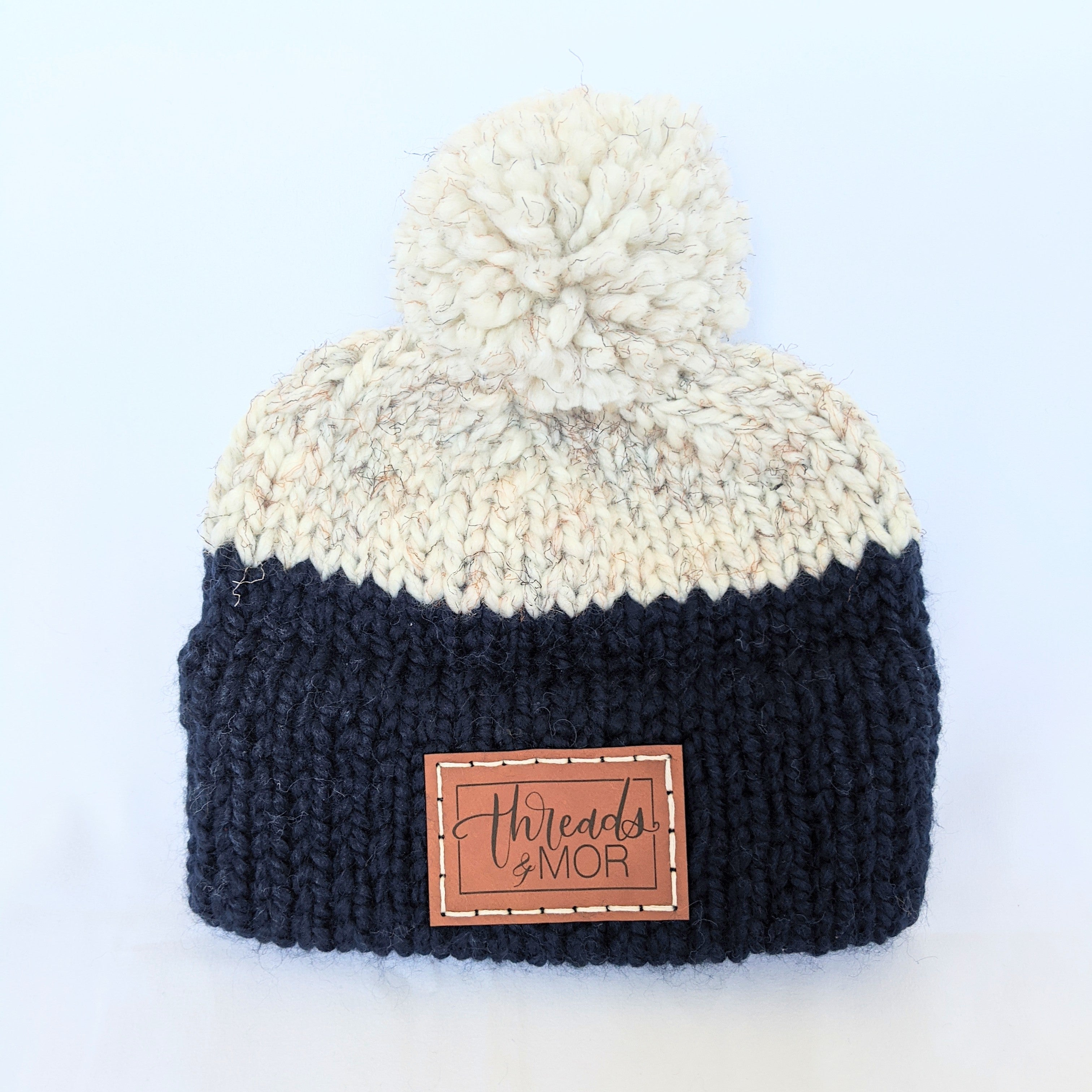 Navy and wheat double brim knit hat with yarn pompom