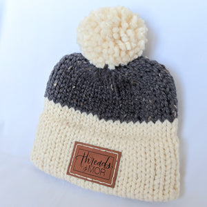 Gray and cream double brim knit hat with yarn pompom