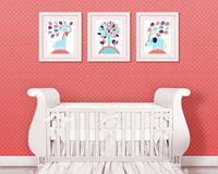 Set of three nursery prints in aqua, coral and navy of an elephant, giraffe and birds all holding a bunch of balloons
