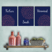 Set of bathroom canvas prints with a navy background, coral dahlia flowers and the words Relax, Soak and Unwind in white lettering.