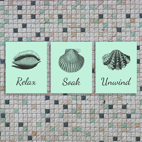 Three bathroom art prints with seashells saying Relax, Soak, and Unwind in a soft mint.