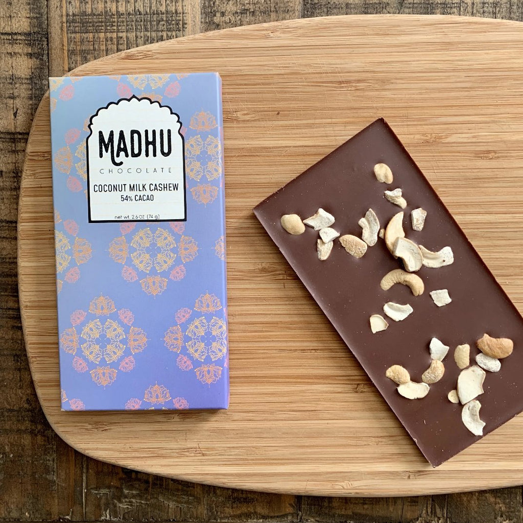 creamy coconut milk chocolate with cashews on a wood background