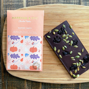 Chocolate bar with toasted pumpkin seeds and dried cherries in a soft orange package.