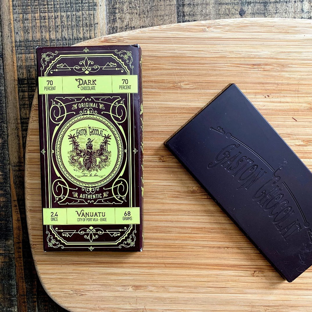 Dark Craft Chocolate bar from Vanuatu on a wood surface.  Extremely deep brown color of craft cacao beans is mouth watering.