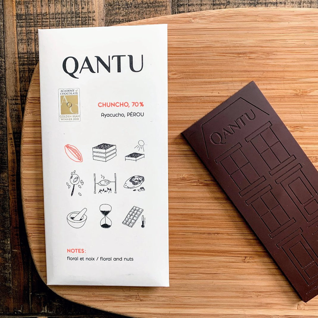 Qantu Chuncho Craft Chocolate bar with a medium-brown tone paired next to its white packaging highlighting symbols of Peru.