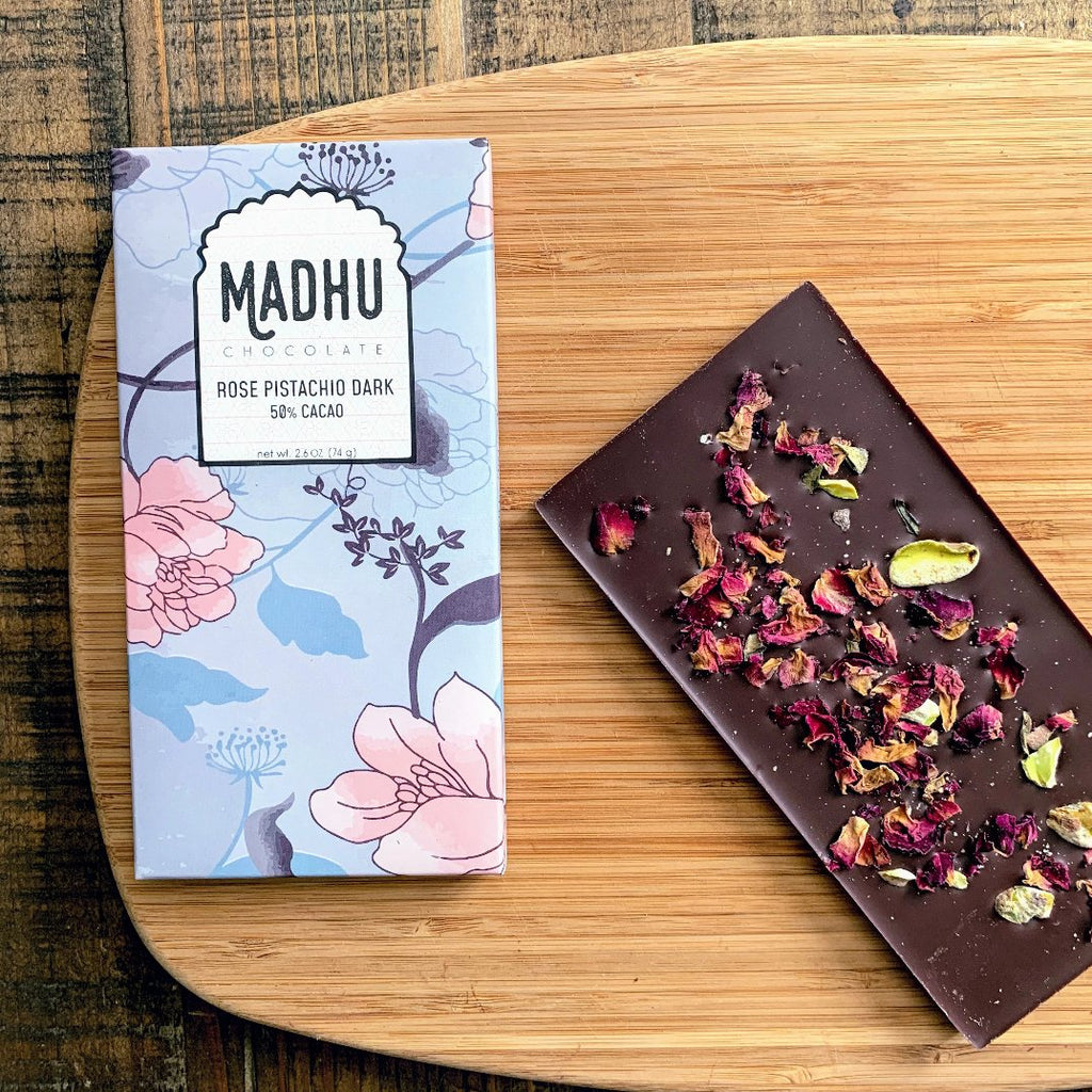 A beautiful contrast of red rose petals and green pistachio on dark Craft Chocolate.  The package features flowers and traditional Indian styling.