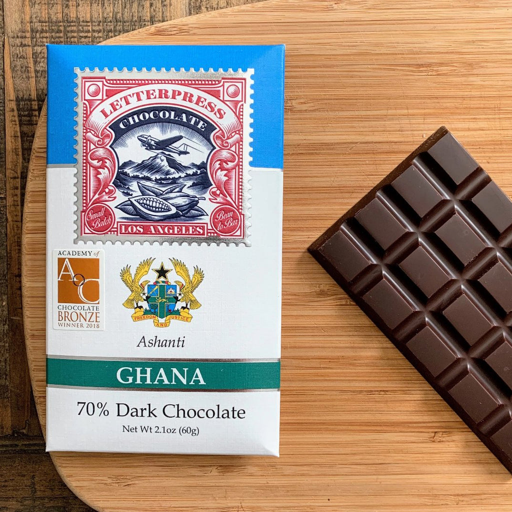 Single Origin Craft Chocolate Bar with deep brown color next to its package that features insignia of Ghana.