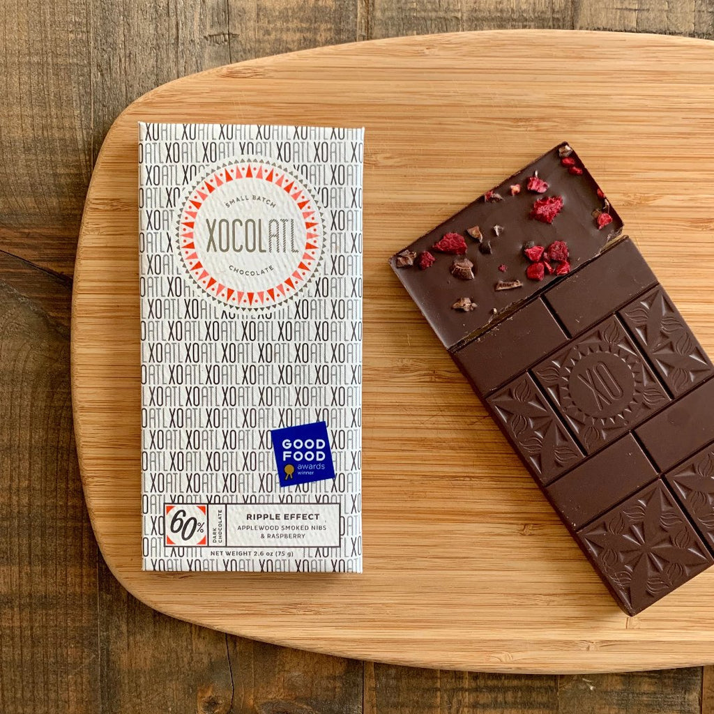 Contrast of dark craft chocolate and bright red raspberries on a smooth wood cutting board.