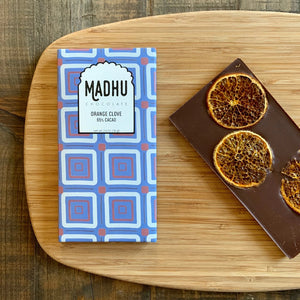 Beautiful orange slices gently folding into Craft Chocolate bar that features traditional Indian geometric pattern on its packaging.
