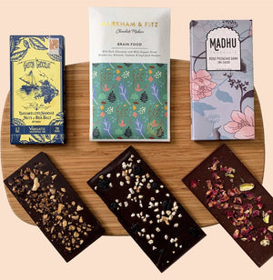 three delicious craft chocolate bars featuring nut inclusions on a hard-grain cutting board