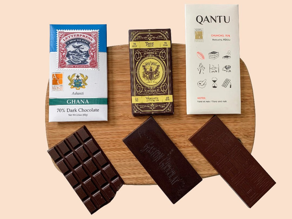 Three single origin craft chocolate bars from Ghana, Vanuatu, and Peru on a wood surface.