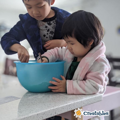 boy and girl stand inlearning tower and are stirring a bowl