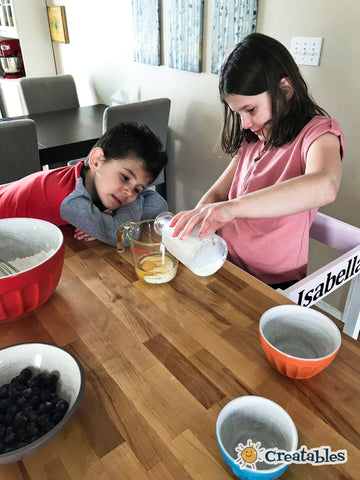 boy watches measuring cup as girl adds milk