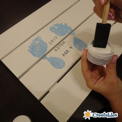 a foam brush is dipping into sealer to apply to a keepsake print