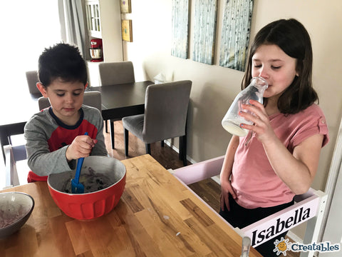 girl drinks milk while boy mixes bowl