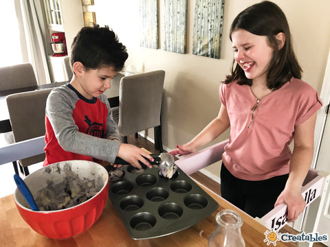 boy scoops batter into muffin tin while girl laughs