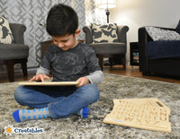 young boy sits crossed legged in livingroom using a finger tracing board and smiling