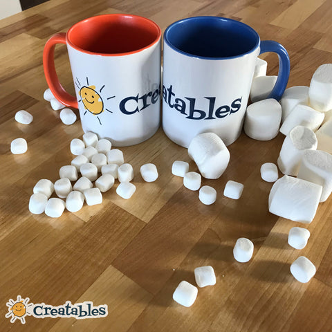 two mugs of hot chocolate sit in a pile of large and small marshmallows on the counter