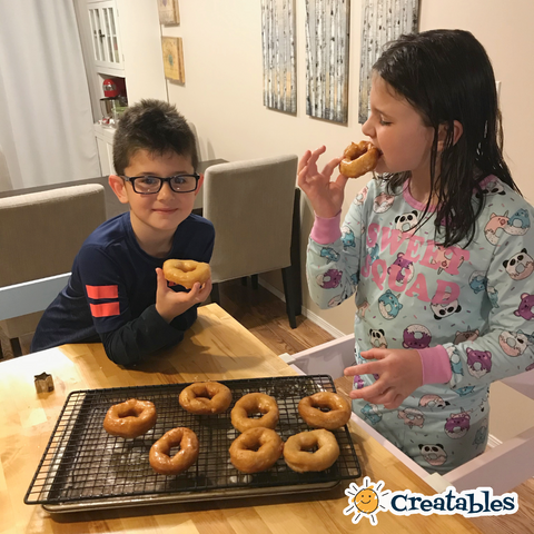 girl and boy take a bite out of fresh made donuts