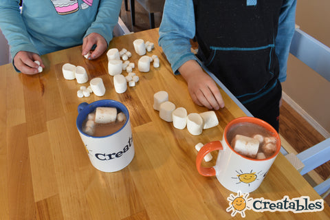 two mugs of hot chocolate with marshmallows in them