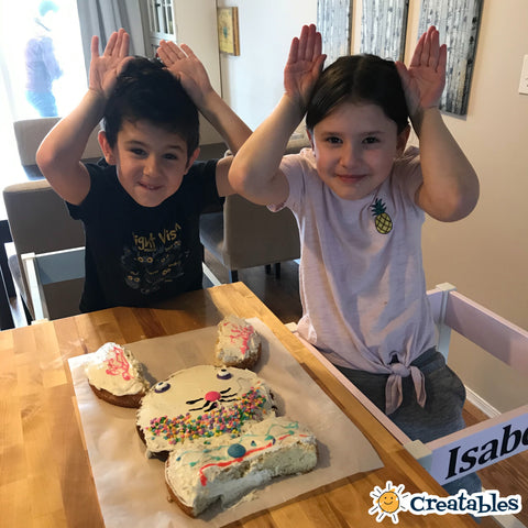 boy and girl hold up bunny ears next to bunny cake