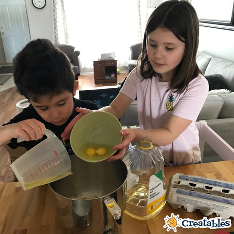 Boy and girl in learning towers add ingredients to a bowl