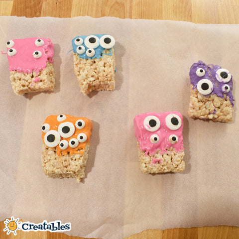 rice krispies dipped in pink, blue, orange, purple chocolate individually with eyeballs