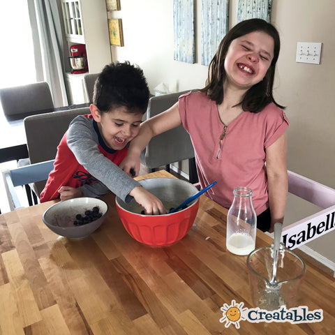 girl and boy in learning tower laugh as they add frozen blueberries to a bowl