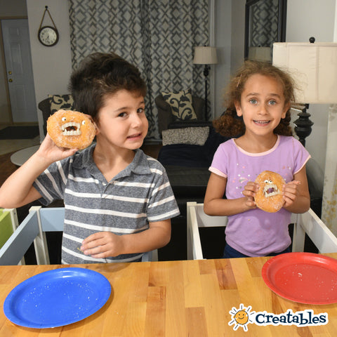 Boy and girl hold up their vampire donuts in while they stand in their Little Sidekicks