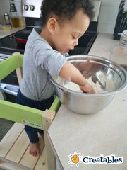 young boy in unpainted Little sidekick with green panels has hands in a bowl of flour