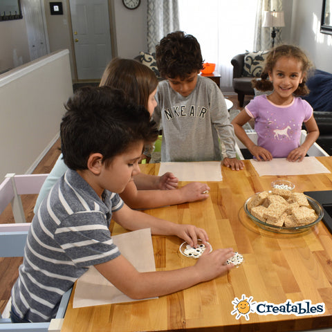 Four kids around a counter looking at their ingredients