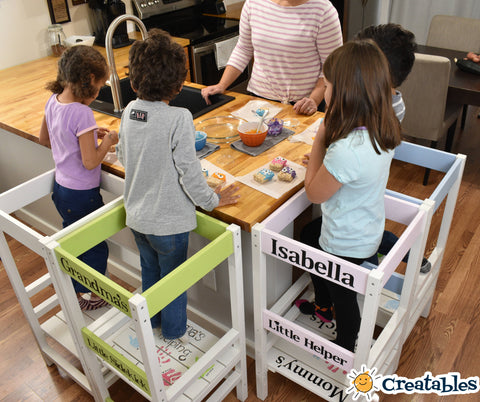 four kids standing in learning towers around the counter