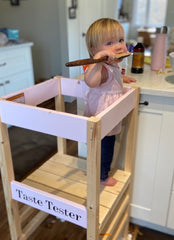 girl in unpainted pick learning tower tastes from a spoon