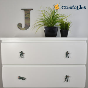 Two drawers of white dresser with two army man knobs on each drawer
