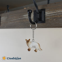 Load image into Gallery viewer, balinese cat white body with brown paws and face keychain on a key rack