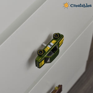 close up of green car drawer knob with yellow stripe on a white dresser