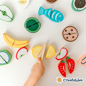assorted play food pieces scattered on a white background. a young hand cut a lemon piece in half with a wooden knife