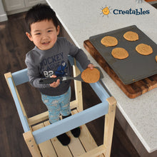 Load image into Gallery viewer, boy in unpainted frame with blue panel little sidekick is in the learning tower looking up and smiling showing off the cookies he made