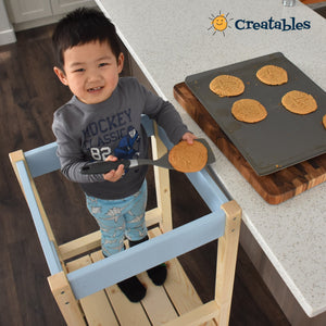 boy in unpainted frame with blue panel little sidekick is in the learning tower looking up and smiling showing off the cookies he made