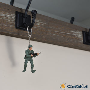 green army man holding gun at waist keychain hangin from a keyrack