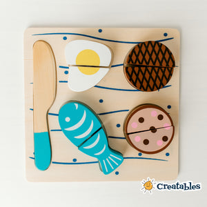 wooden egg, fish, burger and steak with wooden knife on a wooden cutting board decorated with  blue lines and dots