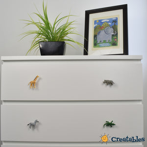 safari drawer knobs on white dresser with elephant kids art picture and a plant on top