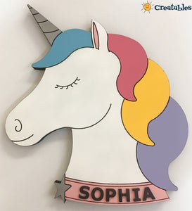Unicorn with sophia on the collar. unicorn has blue, pink, yellow, purple hair and is on a white wall