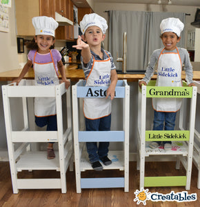 three young children stand in little sidekicks laughing wearing a chef hat and apron.