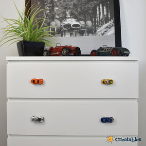 car knobs on white dresser with car decorations on top